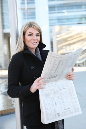 A pretty business woman reading the newspaper outside her company photo