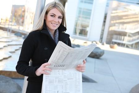 그녀의 회사 외부의 신문을 읽고 예쁜 사업 여자