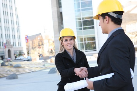 hard working woman: An attractive business construction team shaking hands on the building site Stock Photo