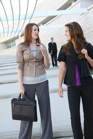 Pretty young business womean walking outside office building photo