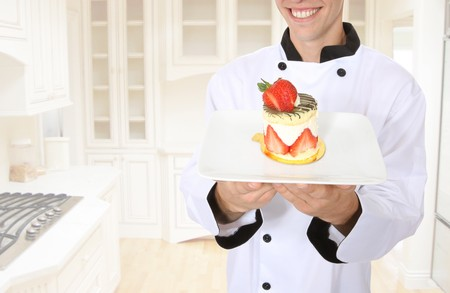 A happy chef holding a dessert in the kitchen Imagens
