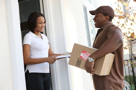 delivering: A handsome young delivery man delivering a package to house Stock Photo