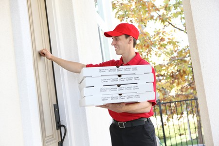 delivery man: A handsome young pizza delivery man holding a pizza