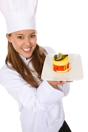 白で分離されたデザートを保持しているきれいな女性シェフ
