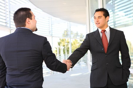 spanish: A business man team handshake at office building Stock Photo