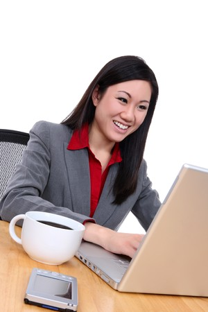 An attractive asian business woman in office on laptop computer photo