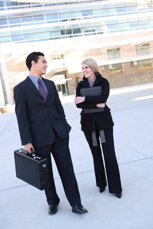Attractive business man and woman walking to work at  office building