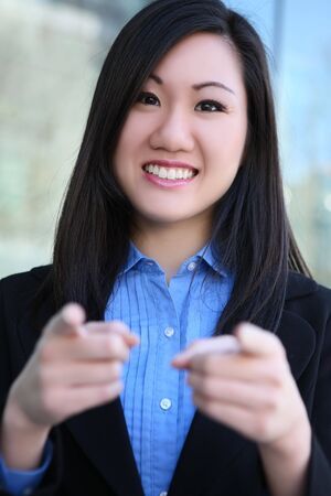 A pretty young asian business woman pointing at office Stock Photo - 4198351