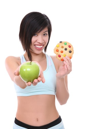 A pretty woman making a choice of good apple or bad cookie