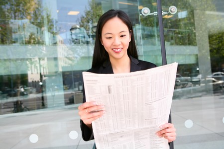 A pretty asian business woman reading the newspaper photo