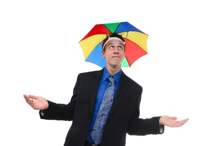 A handsome business man under a rainbow hat umbrella