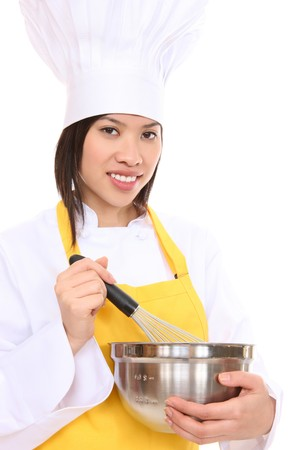 A pretty woman chef holding a whisk and stirring a bowl photo