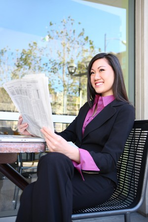 stockbroker: A pretty asian business woman reading the newspaper at office building