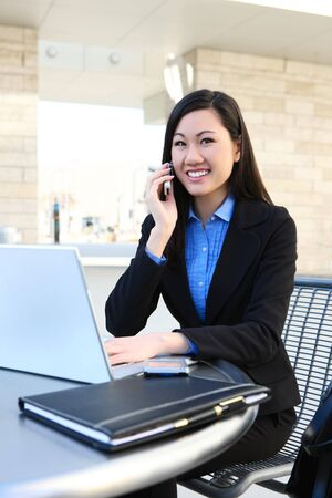 A young, pretty asian business woman at office building on laptop computer photo