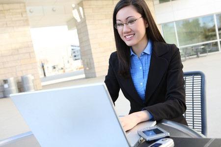 computer model: A young, pretty asian business woman at office building on laptop computer Stock Photo