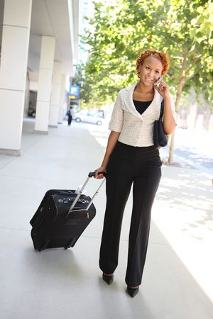 A pretty african american business woman on the cell phone walking to work Stock Photo - 4278179