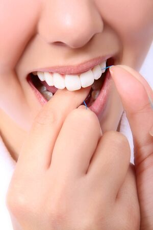 flossing: A cose-up of a woman flossing her teeth