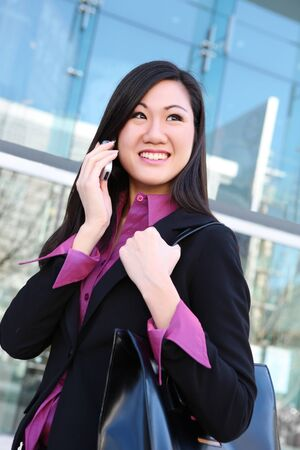 phone business: A young, pretty asian woman business woman at the office