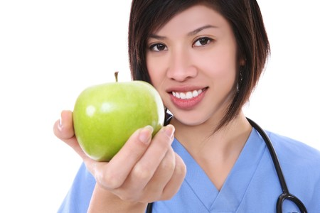 A pretty asian nurse holding a green apple Stock Photo - 4325933