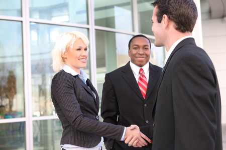 african american handshake:  A diverse ethnic business team shaking hands at office building