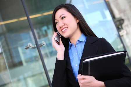 communicate: A young, pretty asian business woman at office building on cell phone