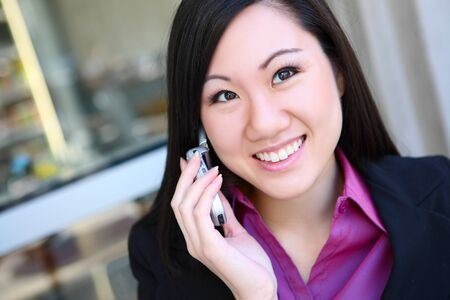 A young, pretty asian business woman at office building on cell phone photo