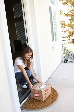 예쁜 여자가 집에서 배달 상자 패키지를 따기 스톡 콘텐츠
