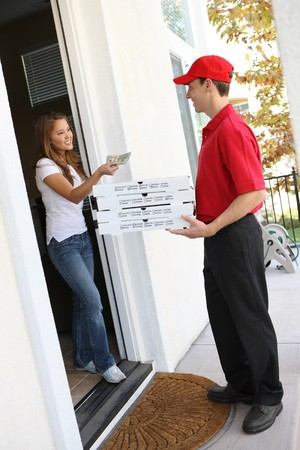 delivery service: A  pizza delivery man giving order to pretty woman