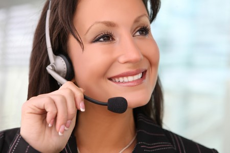 telephonist: A pretty business woman with earphone communicating at office