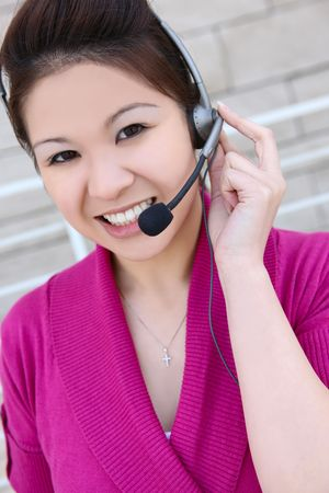 An asian customer service employee thinking and listening to the client