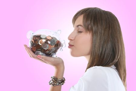 A pretty young business woman kissing her piggy bank