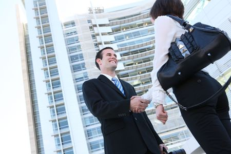 Attractive man and woman business team shaking hands at office building Stock Photo - 4746807