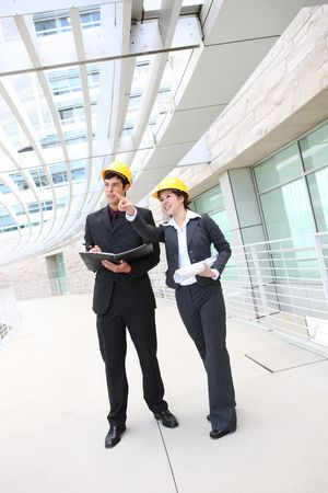 Attractive man and woman architects on building construction site photo