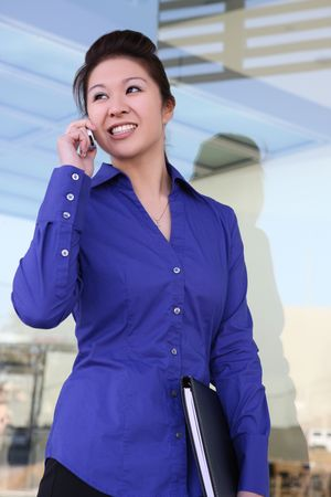 A pretty asian businesswoman talking on the phone outside office Stock Photo - 4746804