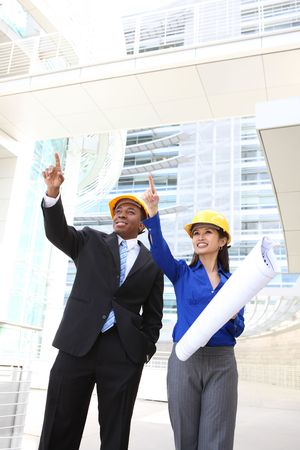 site: A pretty asian woman and african man working as architects on a construction site