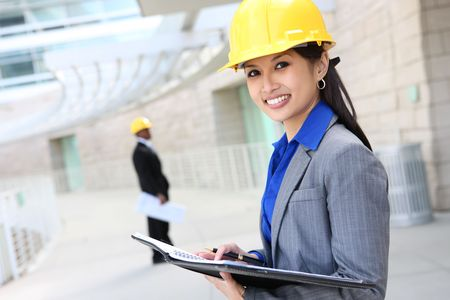 A pretty asian woman working as architect on a construction site Stock Photo - 4843390