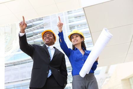A pretty asian woman and african man working as architects on a construction site photo