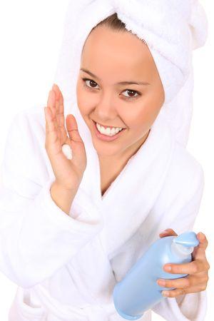 A beautiful woman applying moisturiser cream after shower