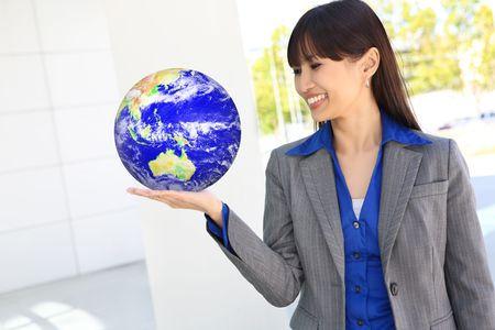holding globe: Una bella donna d'affari asiatici in ufficio azienda globo della terra
