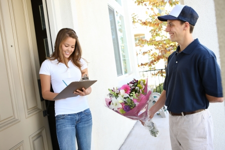 delivery service: A  delivery man giving flowers to pretty woman at home Stock Photo