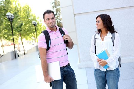 Attractive man and woman students walking to class at college