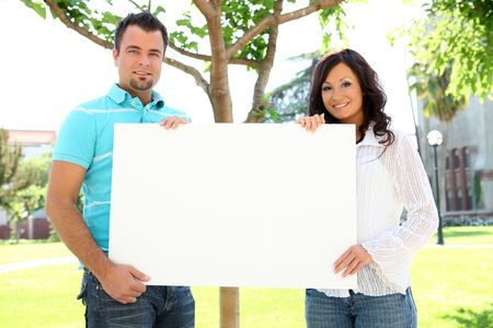 holding blank sign: A young couple man and woman holding blank sign at school