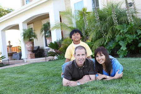 Attractive happy family outside their home having fun Stock Photo - 4981031