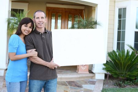 An attractive happy couple in front of their home holding a sign
