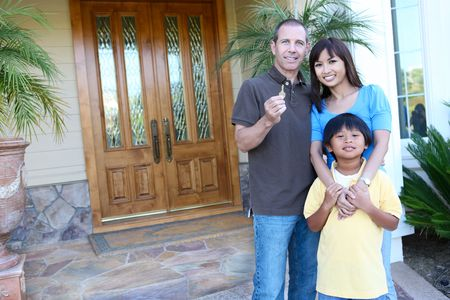 Attractive happy family outside their home with key photo