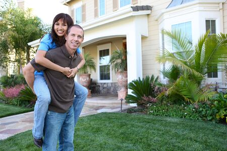 adorable home: An attractive happy couple in front of their home in love
