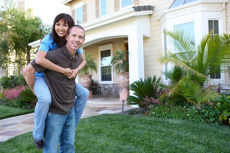Een aantrekkelijke gelukkige paar voor hun huis in de liefde