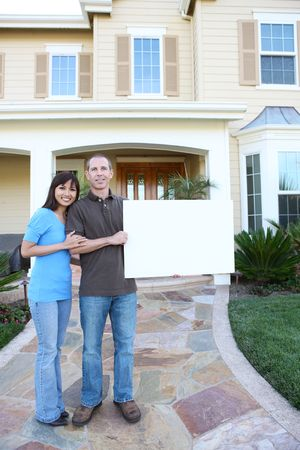 An attractive happy couple in front of their home holding a sign photo