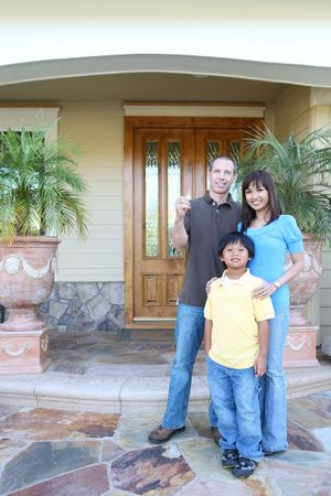 Attractive happy family outside their home with key Stock Photo - 5024564