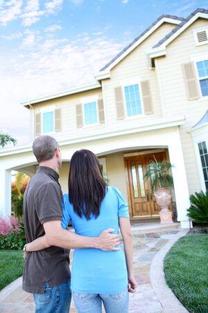 pareja en casa: Una atractiva pareja feliz frente a su casa en el amor